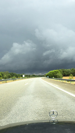 Sunny road with stormy skies ahead